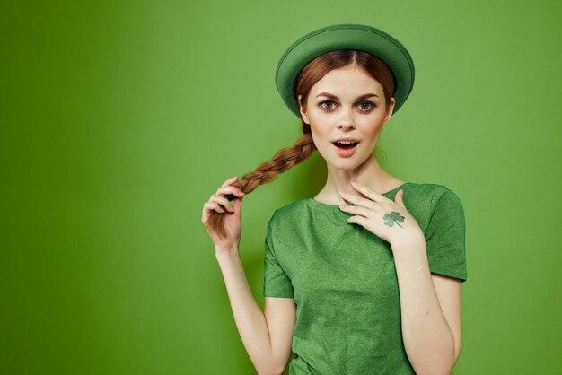 Nettes mädchen mit einem kleeblatt auf ihrer hand an einem grünen feiertags-st. patrick's day-spaßhut auf