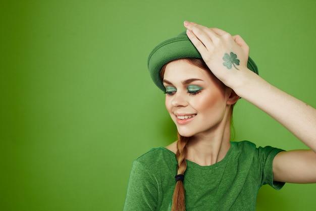 Nettes mädchen mit einem kleeblatt auf ihrer hand auf einem grünen hintergrund feiert st. patrick's day-spaßhut auf ihrem kopf hochwertiges foto