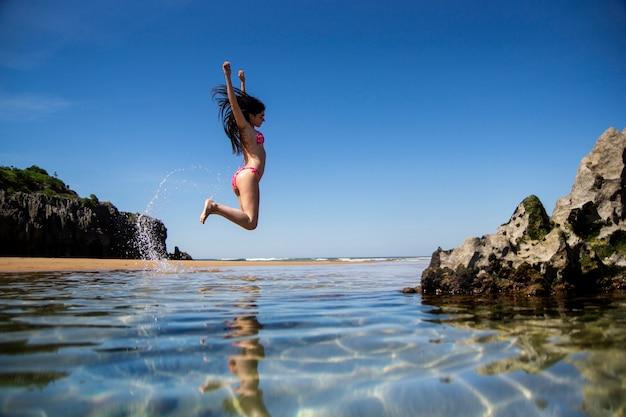 Nettes mädchen mit einem rosa bikini, der auf den strand springt