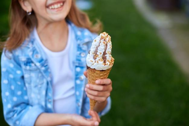 Nettes mädchen mit eistüte lächelnd beim ausruhen im park am sommertag, kind, das eis im freien genießt, schöne ferien, sommerzeit summer
