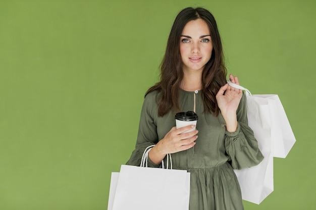 Nettes mädchen mit kaffee und vielen einkaufsnetzen auf grünem hintergrund