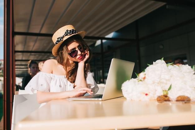 Nettes mädchen mit langen haaren im hut sitzt am tisch auf der terrasse im café. sie trägt ein weißes kleid mit nackten schultern, rotem lippenstift und sonnenbrille. sie sieht verärgert aus.