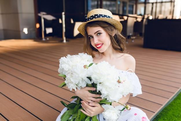 Nettes mädchen mit langen haaren im hut sitzt auf dem boden auf der terrasse. sie trägt ein weißes kleid mit nackten schultern und rotem lippenstift. sie hat weiße blumen in den händen und lächelt.