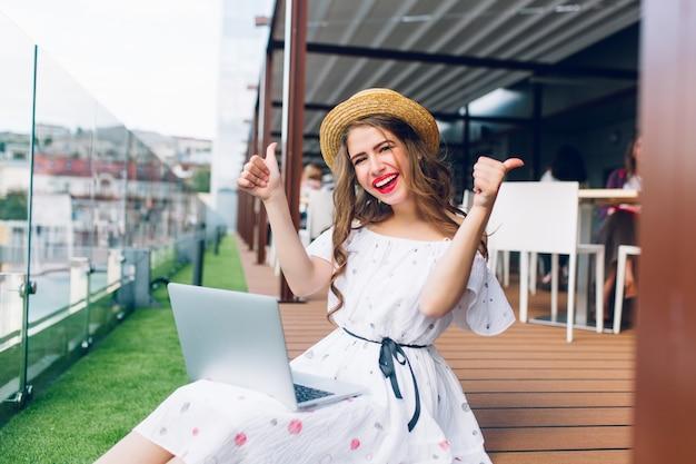 Nettes mädchen mit langen haaren sitzt auf dem boden auf der terrasse. sie trägt ein weißes kleid mit nackten schultern, rotem lippenstift und hut. sie hat einen laptop auf den knien und lächelt in die kamera.
