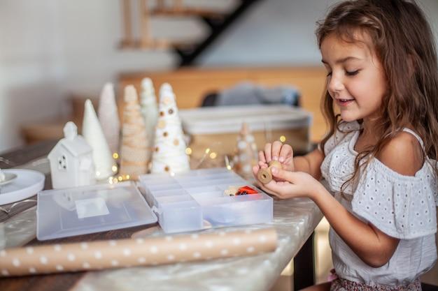 Nettes mädchen mit lockigem haar fertigt und verziert papierkegel-weihnachtsbaum mit knöpfen, garn und lichterketten.