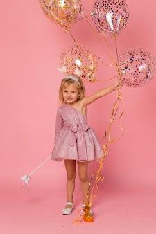 Nettes mädchen mit luftballons und zauberstab