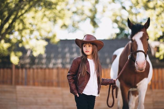 Nettes mädchen mit pferd an der ranch