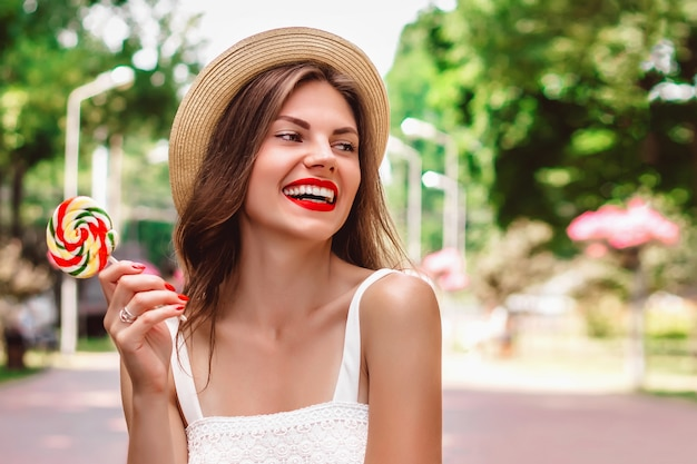 Nettes mädchen mit rotem lippenstift in einem strohhut und einem lutscher in ihren händen lacht und lächelt im park für text. sommermädchen geht spazieren und hat spaß auf den straßen der stadt