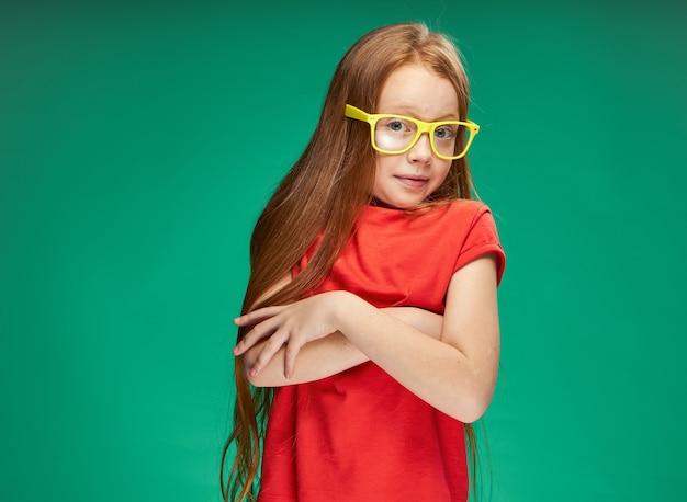 Nettes mädchen mit roten haaren gelben brillen emotionen studio grün