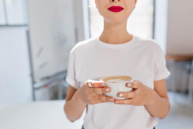 Nettes mädchen mit roten lippen und trendiger maniküre, die tasse des leckeren kaffees hält, der geschmack im arbeitsreichen tag genießt