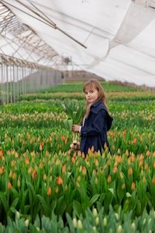 Nettes mädchen mit tulpen mit blondem haar frühling in einem gewächshaus mit wachsenden tulpen