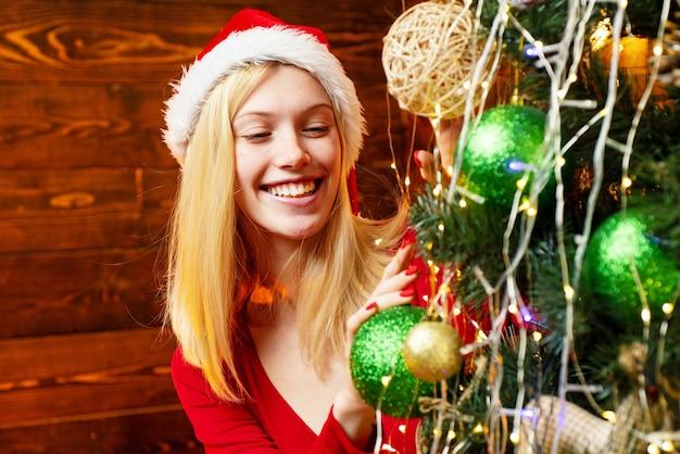 Nettes mädchen schmückt den weihnachtsbaum drinnen. weihnachtsdekorationen. modeporträt des modells