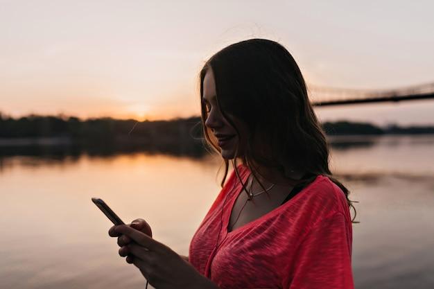Nettes mädchen sms-nachricht mit lächeln auf natur. charmante europäische frau, die mit telefon nahe fluss aufwirft.