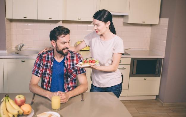 Nettes mädchen steht neben kerl und gibt ihm einen teller mit omelett und kirschtomaten. er sieht es an und lächelt. guy hat hunger. er sitzt am tisch. es gibt obst und ein glas saft.