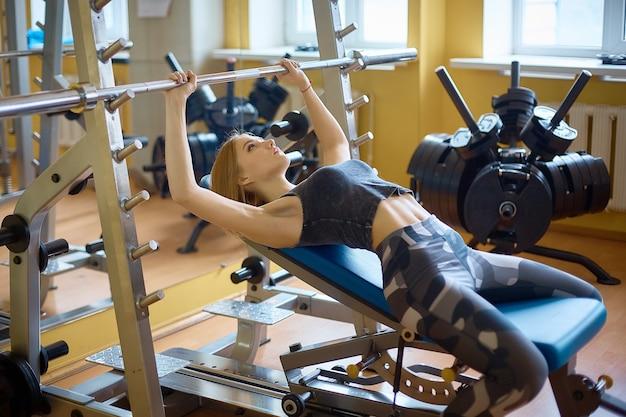 Nettes mädchen, übungen auf dem simulator machend. gesunde lebensweise, sport treiben