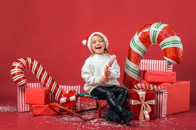 Nettes mädchen umgeben von weihnachtsgeschenken und -elementen