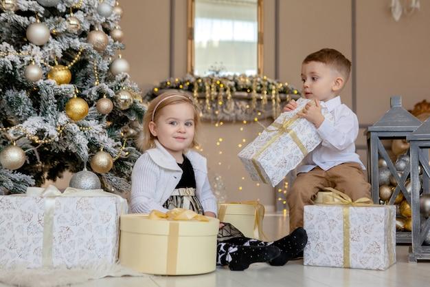 Nettes mädchen und junge, die weihnachtsgeschenke öffnen. kinder unter weihnachtsbaum mit geschenkboxen. dekoriertes wohnzimmer mit traditionellem kamin. gemütlicher warmer winterabend zu hause.