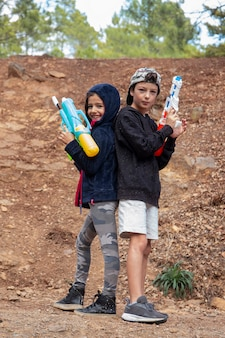 Nettes mädchen und junge mit wasserpistolen