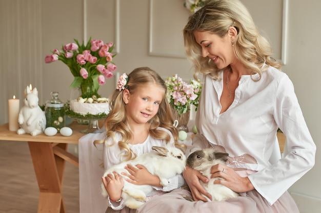 Nettes mädchen und mutter spielen mit kaninchen