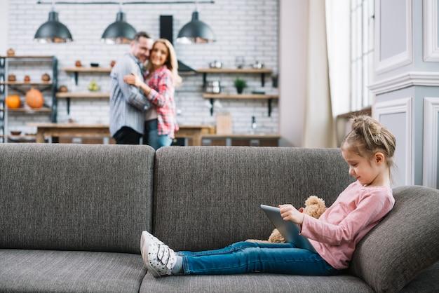 Nettes mädchen, welches die digitale tablette sitzt auf couch verwendet