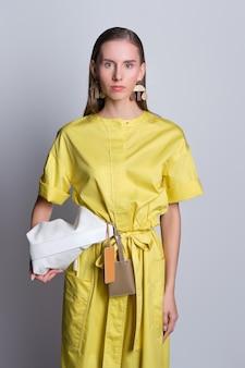 Nettes mode-modell im gelben kleid mit handtasche