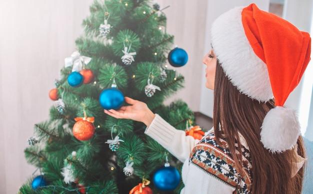 Nettes modell im roten hut steht nahe weihnachtsbaum und verziert ihn. sie hält die hand unter blauem spielzeug.