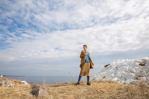 Nettes modell mit kurzem haarschnitt, der in der nördlichen landschaft in voller höhe mit etwas schnee und gelbem gras posiert und senfstrickkostüm trägt.