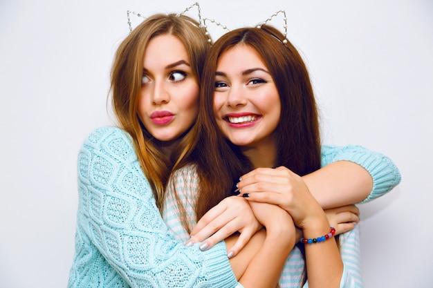 Nettes modeporträt von hübschen schwesternfrauen, die spaß zusammen umarmungen haben und verrückt werden, lustige katzenohren, minzwinterpullover, weiße wand, beste freunde, freude, trend, beziehungen, glückliches, natürliches make-up.