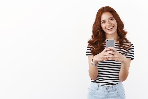 Nettes modernes tausendjähriges mädchen mit roter lockiger frisur, freudiger kopfneigung, enthusiastisches lächeln, smartphone halten, selfie im spiegel machen, doofes grinsen machen, freunde benachrichtigen, weiße wand
