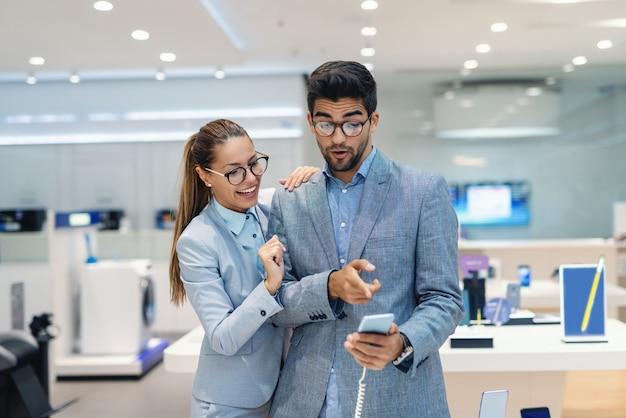 Nettes multikulturelles paar gekleidet elegant, das neues smartphone im tech store wählt. mann zeigt auf smartphone.