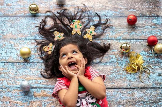 Nettes nettes lächelndes mädchen mit dem verzierten weihnachtshaar