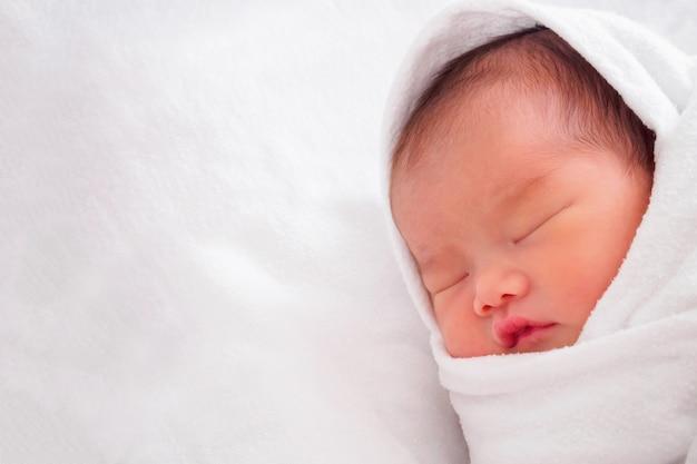 Nettes neugeborenes asiatisches baby, das auf weißem stoff schläft