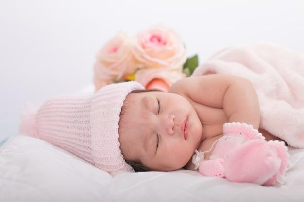 Nettes neugeborenes asiatisches mädchen, das auf dem bett ohne kleidung schläft. süßer rosafarbener hintergrund.