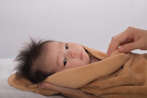 Nettes neugeborenes asiatisches mädchen, das auf dem bett schläft.