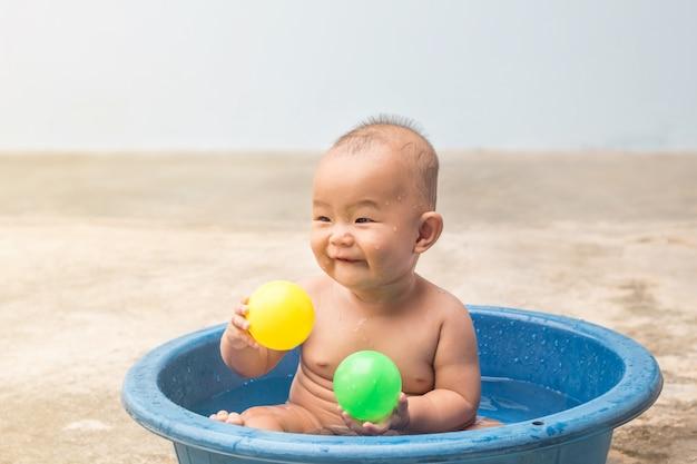 Nettes neugeborenes baby, das ball im plastikbecken während der dusche, lernende kinder spielt