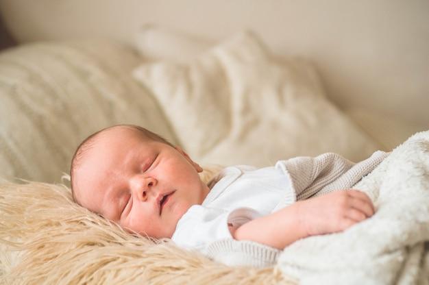 Nettes neugeborenes baby schlafend eingewickelt in ein weiches plaid. liebe baby. neugeborenes baby und mutter.