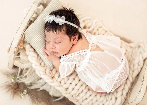 Nettes neugeborenes, das auf kleinem bett schläft