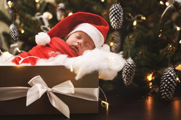 Nettes neugeborenes, das weihnachtsmannmütze trägt, schläft in der weihnachtsgeschenkbox. frohe weihnachten und ein glückliches neues jahr.