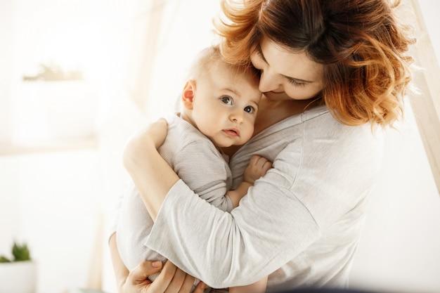Nettes neugeborenes kind schaut erschrocken zur seite, während gut aussehende junge mutter sanft baby umarmt, das ihre liebe und unterstützung ausdrückt. familienkonzept.