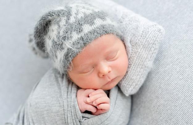 Nettes neugeborenes schlafend auf winzigem kissen, das auf seite liegt
