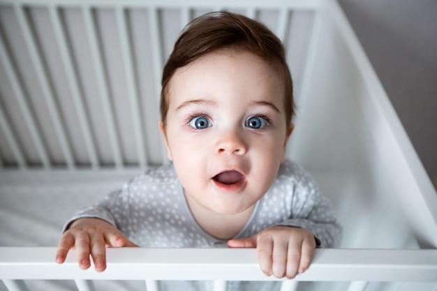Nettes neugieriges baby, das in einem weißen krippenbett steht.
