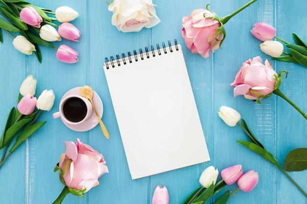 Nettes notizbuch umgeben durch tulpen und rosen auf einem blauen hölzernen