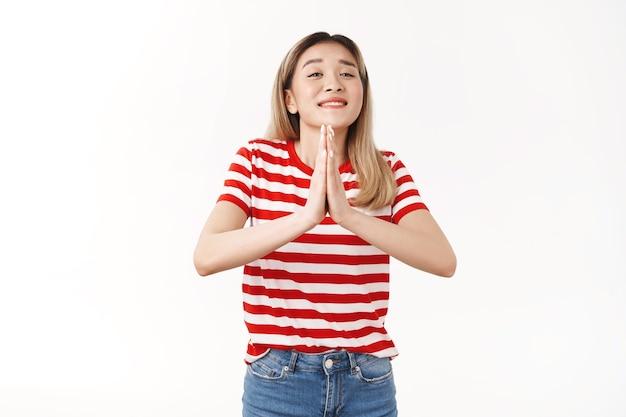 Nettes optimistisches dummes blondes asiatisches mädchen, das freund bettelt, hand leihen, handflächen zusammendrücken, beten, geste schließen augen, die breit flehend lächeln, wünsche flehentlich positive stimmung machen