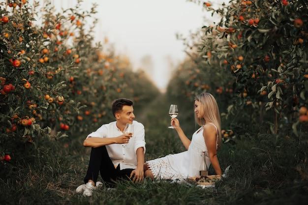 Nettes paar auf picknick, das auf einem grünen gras im apfelgarten sitzt. romantisches paar, das sich gegenseitig mit wein röstet, während es zusammen auf picknick sitzt.