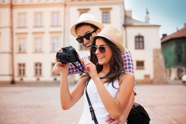 Nettes paar, das auf ihren fotos vor der kamera schaut