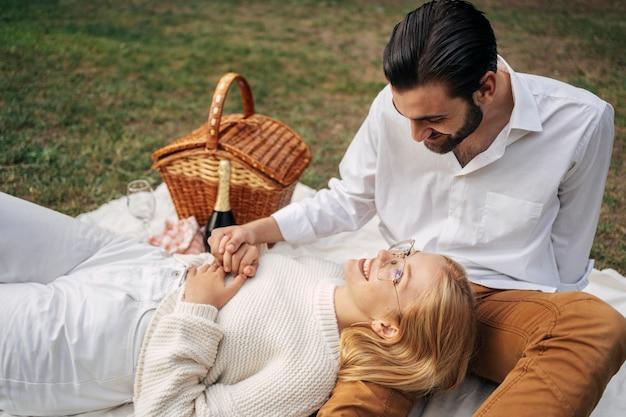 Nettes paar, das ein picknick zusammen im freien hat