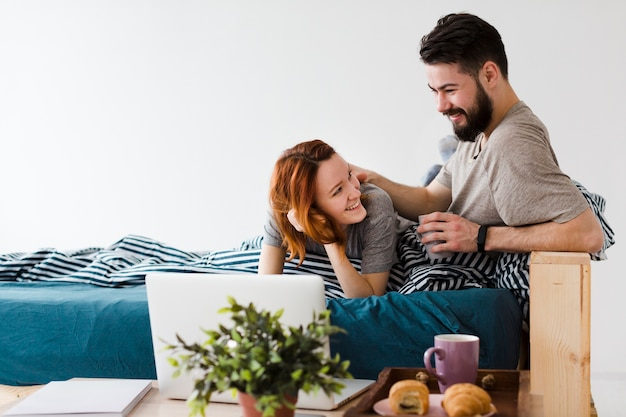 Nettes paar, das einander und laptop ansieht
