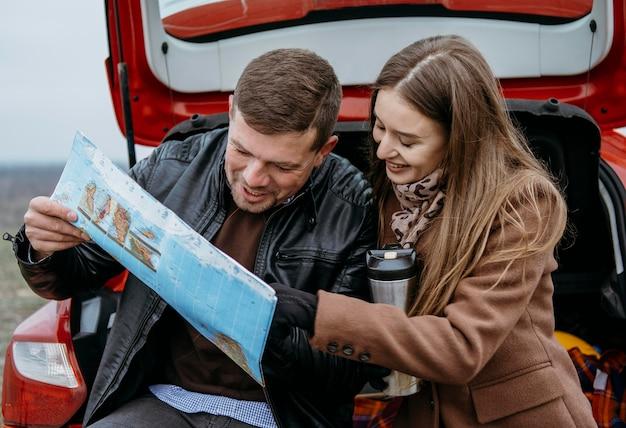 Nettes paar, das eine karte im kofferraum des autos überprüft