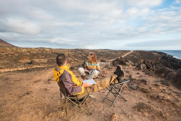 Nettes paar, das einen sonnenuntergang am ende des tages genießt, reist im fernweh für glückliche kakukasier, die alternatives büro mit laptop und mobiler verbindung zu internetfotografen arbeiten