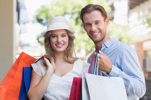 Nettes paar, das einkaufstaschen hält